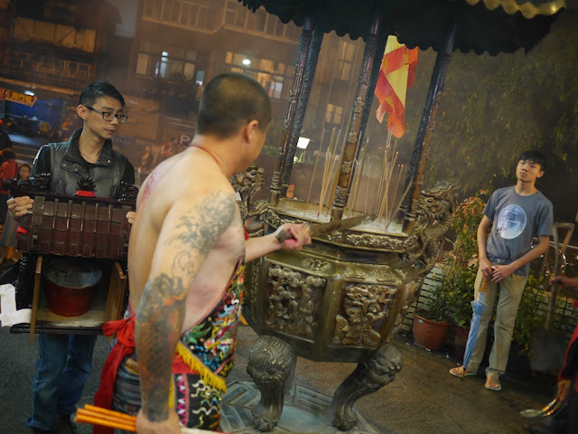 man sticking a sword into ashes for a ceremony at the Chang Qing Temple (長慶廟) in Taipei