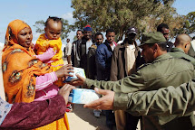 Tunisian soldiers dispense milk  to evacuees who fled the violence in Libya during a food distribution at the United Nations High Commissioner for Refugees (UNHCR) refugee camp near the border crossing of Ras March 23, 2011. REUTERS/Anis Mili (TUNISIA - T