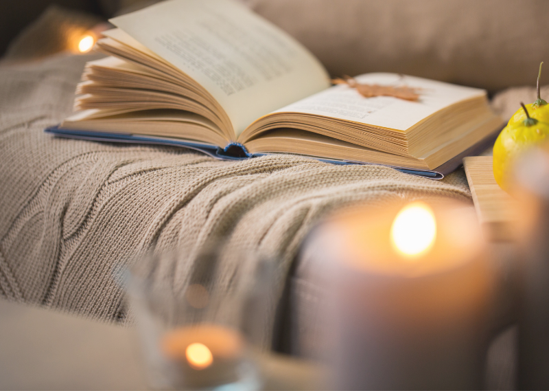 A lit candle and a book on the sofa in a post about five simple ways to feel cosy this Autumn.