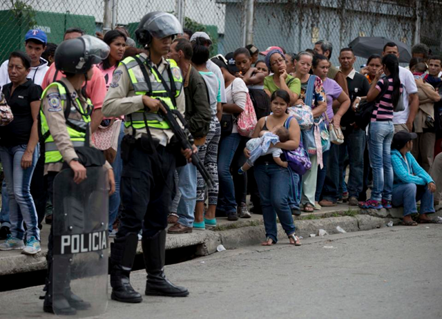 In this 1 June 2016 photo, police stand guard by customers waiting their turn outside a supermarket to buy price-regulated groceries in the Petare shantytown in Caracas, Venezuela. Government officials blame the country's food shortage on right-wing business owners hoarding products to sow chaos, while their detractors say it's the result of chronic economic mismanagement. Some are turning to urban farming to get vegetables, an unaffordable luxury for many, back into their diets. Photo: Fernando Llano / AP Photo