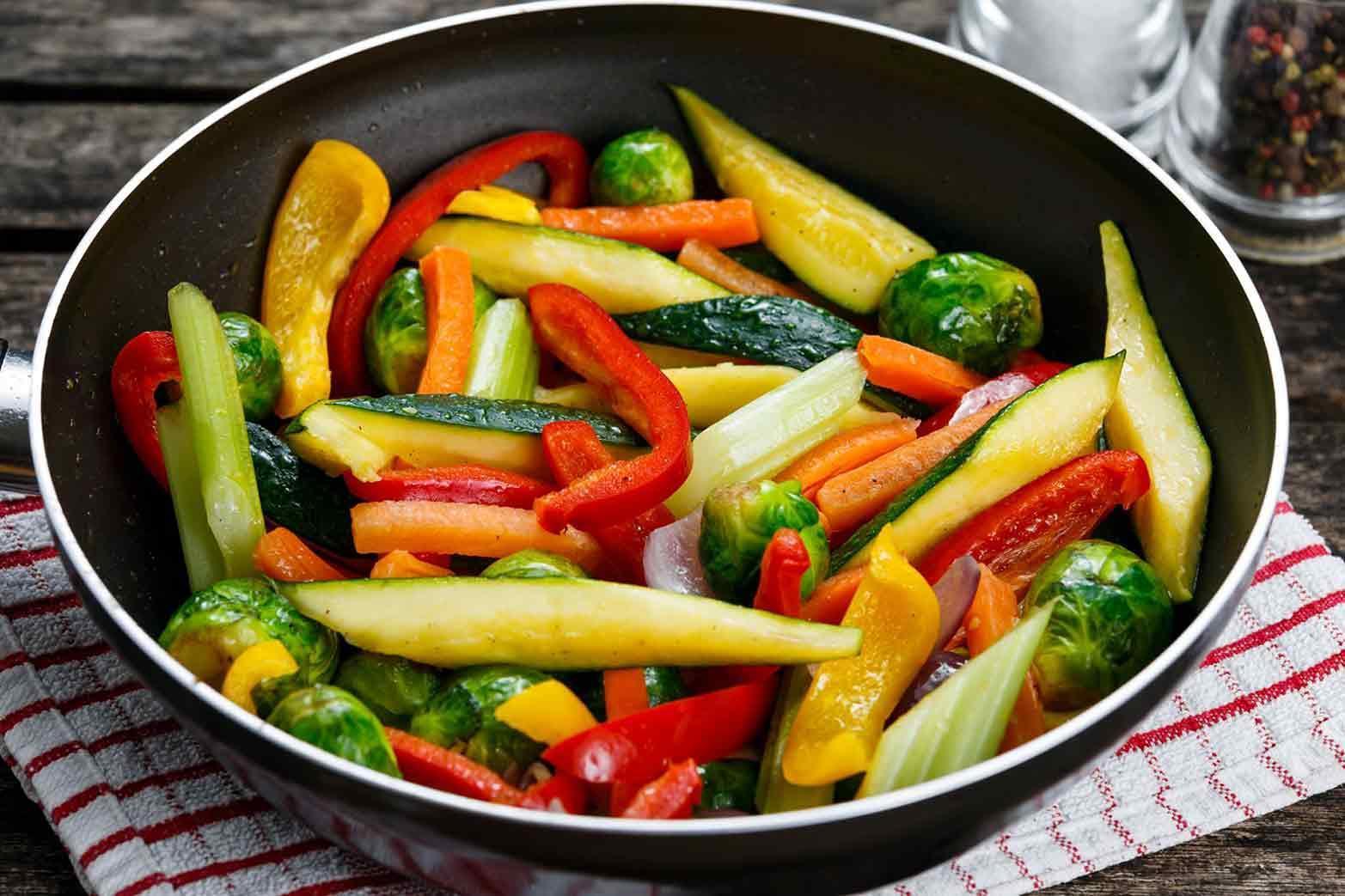 Légumes rôtis cuits dans une poêle sur table en bois.