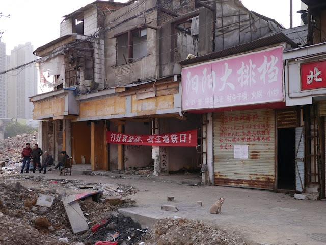 women standing and a dog sitting outside some remaining buildings at Beizheng Street in Changsha