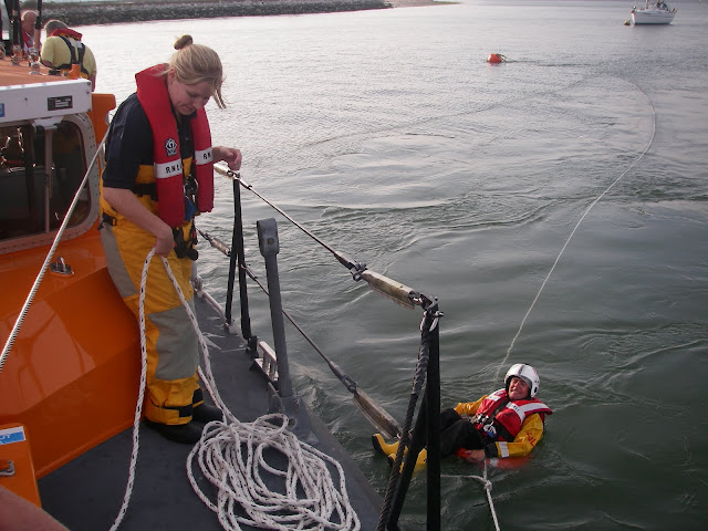 Crew members using a breeches buoy
