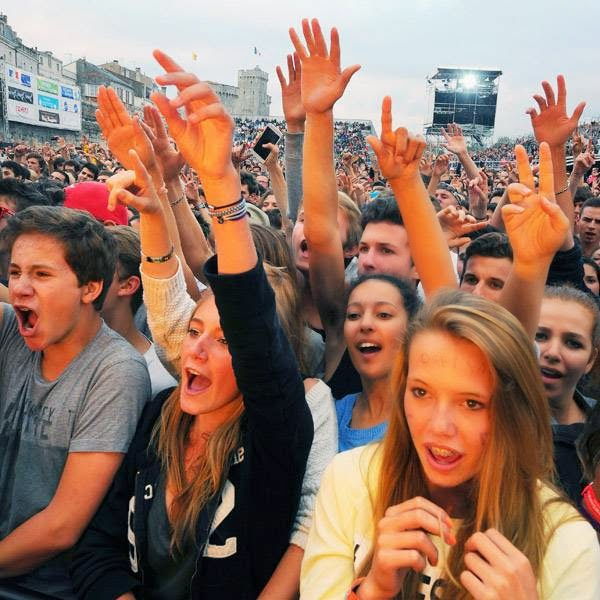 People cheer as they listen to a concert given on the main stage by French rapper Akhenaton of the band IAM (unseen) on July 13, 2014 in La Rochelle, during the Francofolies music Festival.