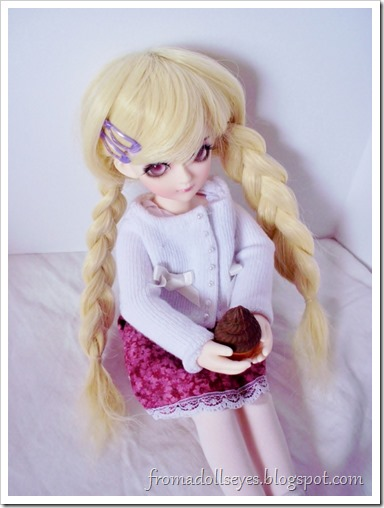 A ball jointed doll eating a chocolate ice cream cone while wearing a white sweater.  Stains just waiting to happen.