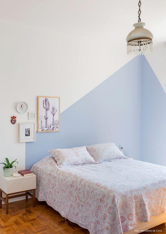 Quarto com cama de casal e parede da cabeceira pintada de forma geométrica azul e restante branco, quadros decorativos, piso de madeira e criado mudo branco