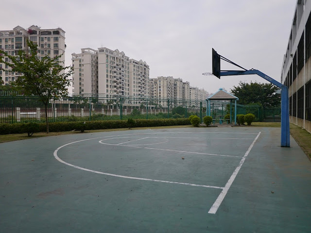 A partial basketball court in Macau in sight of apartments in Zhuhai
