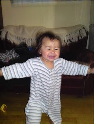Skrattande / leende barn i randig sparkdräkt, gående med öppna armar,