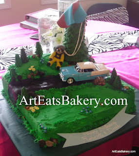 Skydiver custom butter cream birthday cake with edible parachute, trees, rocks, flowers and grass. The Belaire car is a die cast model