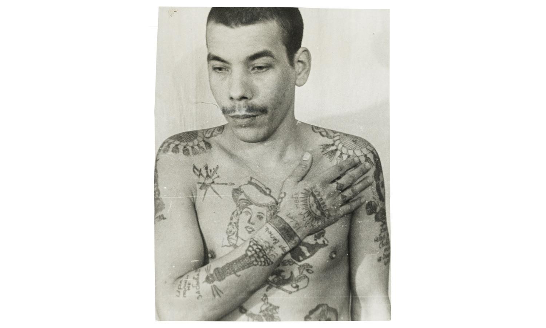Этот заключённый не авторитет воровского мира, но пытался притвориться им с помощью татуировок, которые должны были повысить его положение в тюремной иерархии. Маяк на правой руке обозначает стремление к свободе. Наручники на каждом запястье говорят о том, что он приговорен больше, чем к пяти годам заключения.