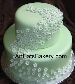Two tier mint green fondant custom wedding cake with tiny white flowers
