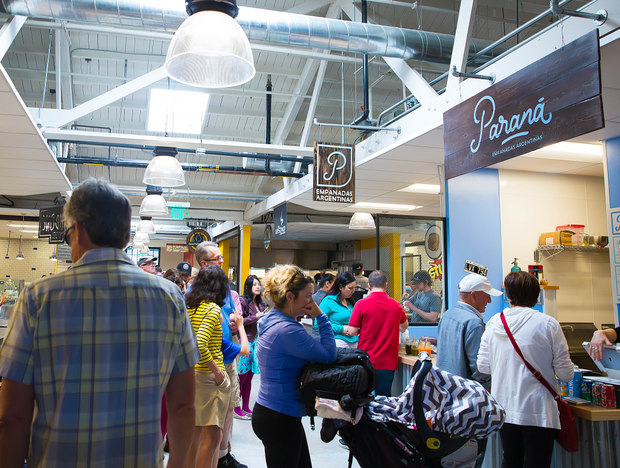 photo of people waiting in line at different booths in the food hall