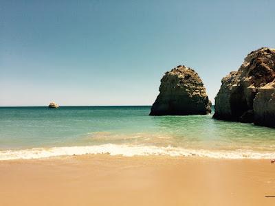Sikten ut mot havet. 2 klipper nær stranden. En annen lenger ute.