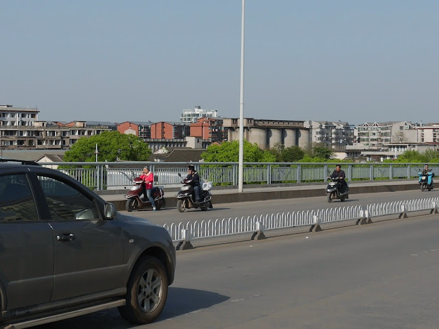 man using a mobile phone while riding a motorbike and looking at a woman who stopped her motorbike to use a mobile phone