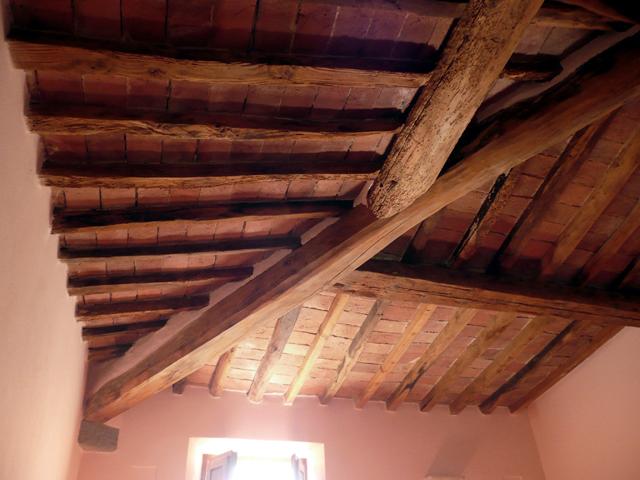 pareti rosa, travi in legno, casa rustica