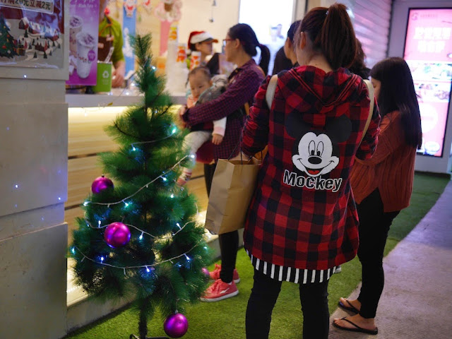 "young woman wearing a ""Mockey Mouse"" coat standing next to a Christmas tree in Xiamen, China"