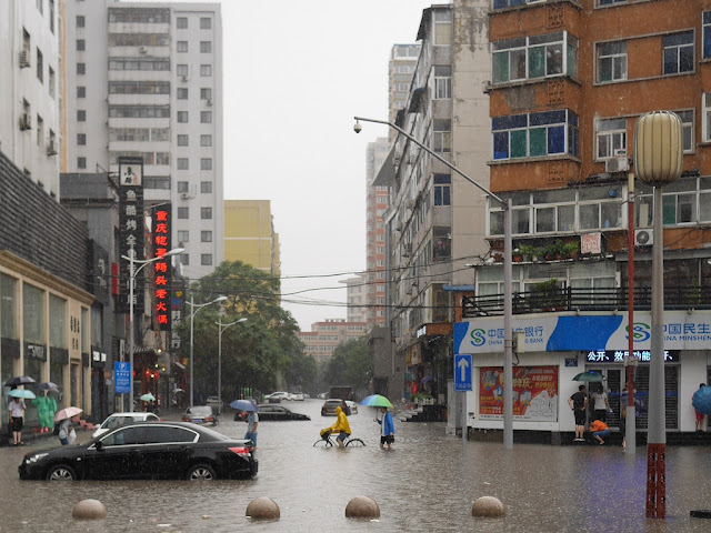 stalled car, person riding a bicycle, and people walking on a flooded street in Taiyuan, China