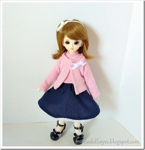 A yosd ball jointed doll wearing a cute pink sweater set with a navy blue a-line skirt and a bow pin on the sweater.  We will learn how to make this cute outfit.