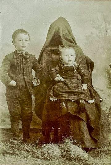 Mãe escondida por pano e seus dois filhos