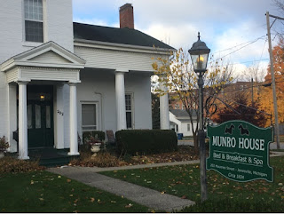Green B&B sign in front of white mansion with trees in red and yellow fall colors