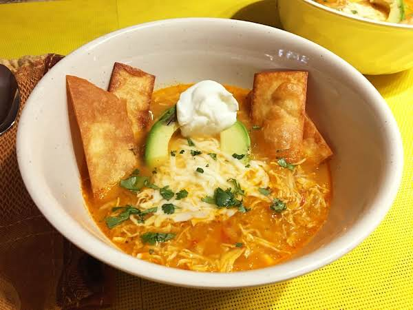 A Soup Bowl Garnished With A Dollop Of Sour Cream, Fried Tortilla Chips, An Avocado Slice And Chopped Cilantro.