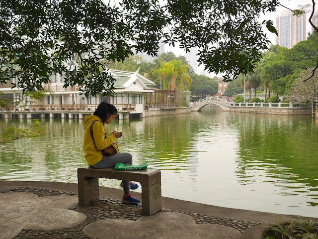 girl using a mobile device sitting on a stone bench next to a lake at Zhongshan Park in Xiamen