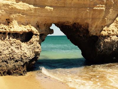 En grotte gjennom en klippe på stranden. Vannkanten rekker akkurat opp til åpningen.