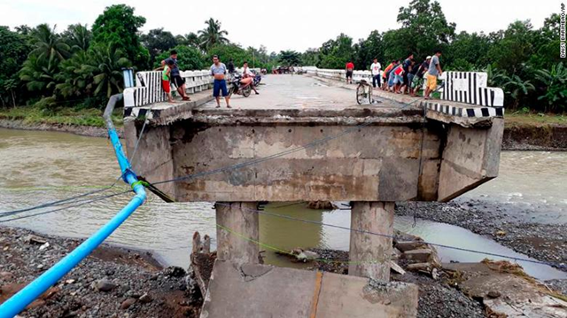 People gather on a bridge which was damaged by flooding Sunday, 24 December 2017, after Tropical Storm Tembin dumped heavy rains on the area. Tembin is the Philippines' second deadly tropical storm in a month. Photo: Daisy Barimbao / AP