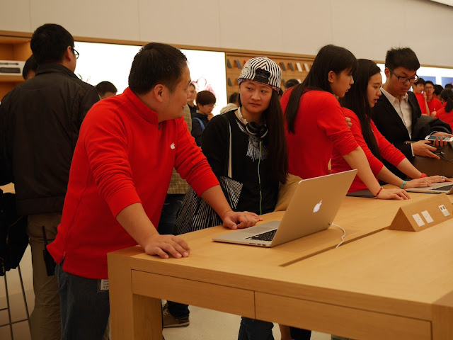 Apple employee assisting a customer with a laptop