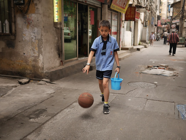 boy with a basketball and a bucket at Wuya Lane in Shaoguan, Guangdong