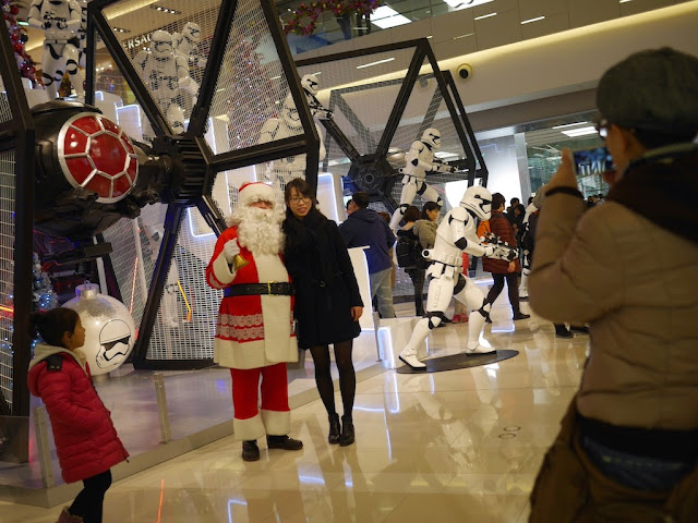 young woman posing with Santa Claus in front of a Star Wars TIE fighter at the IAPM shopping center in Shanghai