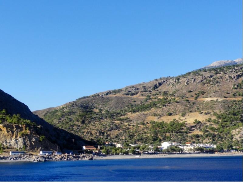 Liten by sett fra sjøen. Fjell og et dalføre i bakgrunnen.