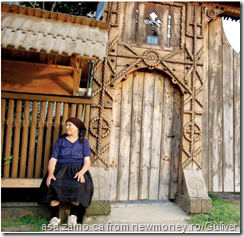 old lady in front of traditional village style wooden gate