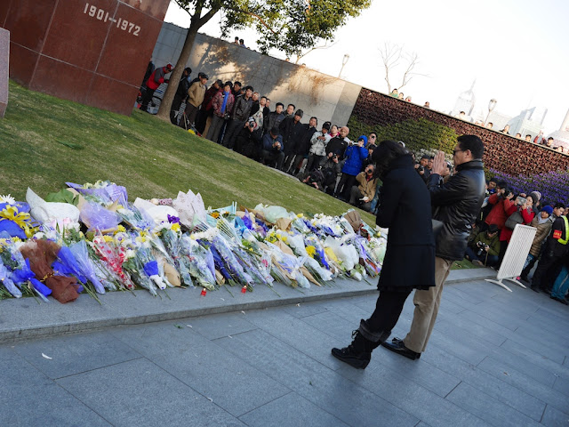 womand and man praying in front of a memorial for people killed and injured by the New Year's Eve stampede in Shanghai