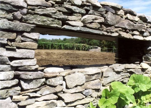 Stone walls enclose a vegetable garden.