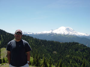 Photo of Nick Peyton and Mount Rainer on top Noble Knob on July 9, 2006. Photo courtesy of Nick Peyton.