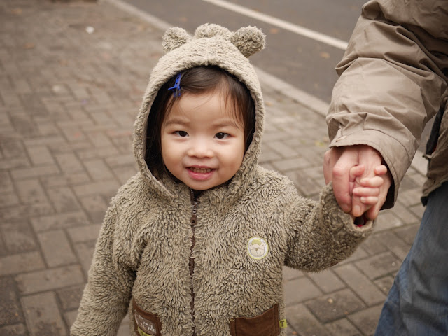 little girl wearing a bear-themed coat