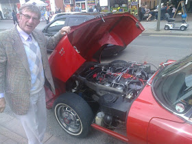 Owner standing with bonnet up to sports car