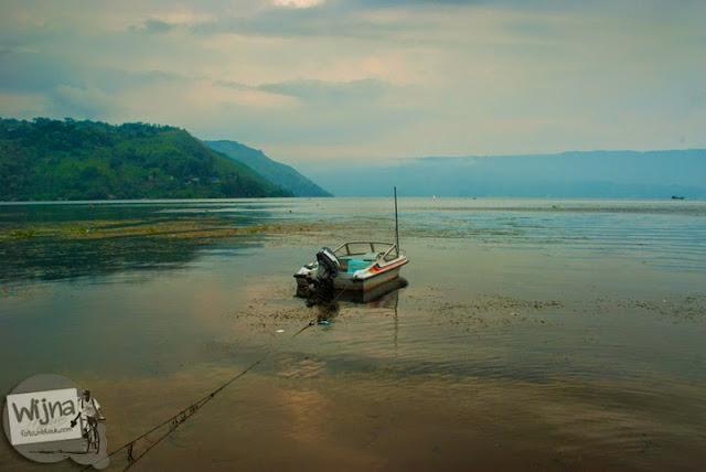 Sebuah kapal motor nampak rusak dan tidak terawat itu ditambatkan di lepas kotornya danau Toba di Kota Parapat, Sumatera Utara