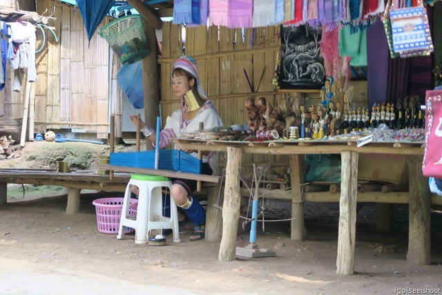 Karen hill-tribe women do weaving work or sell handicraft in front of their huts