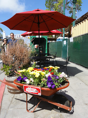 Trillebår med blomster for to bord.