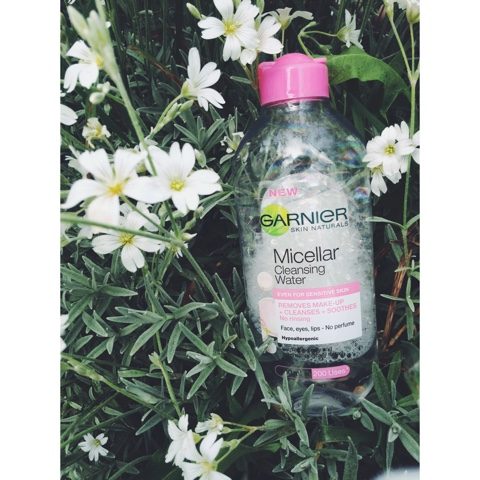 Close up of the Garnier Micellar Water sitting in amongst some white flowers