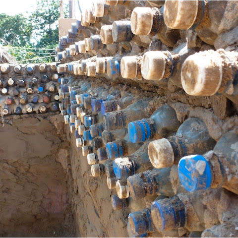 A wall constructed out of plastic bottles filled with local soil.