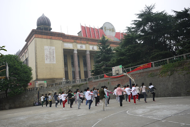 students in a fitness class at a basketball court in front of the library at Hunan First Normal University in Changsha, China