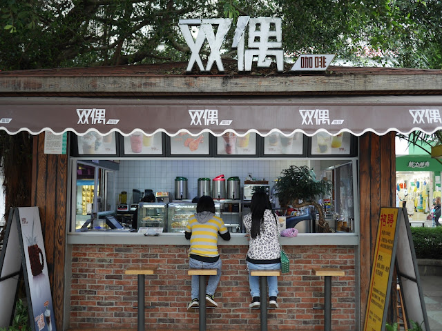 two people sitting at an outdoor cafe in Zhanjiang, China