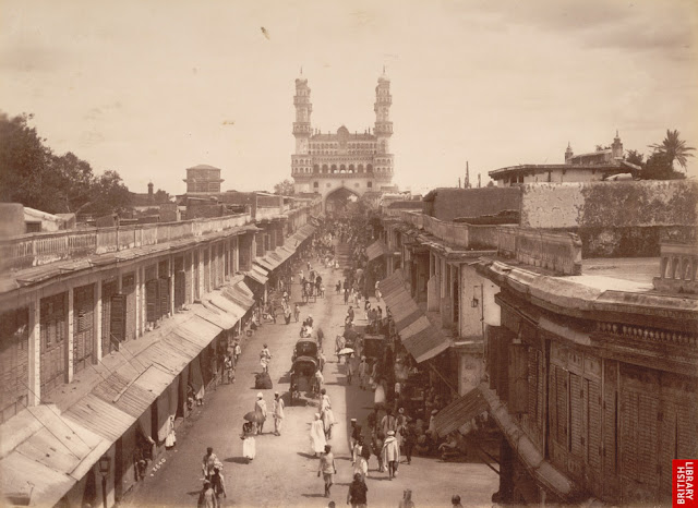Photograph of a main street in Hyderabad, looking towards the Char Minar, taken by Deen Dayal in the 1880s. This is from the Curzon Collection: 'Views of HH the Nizam's Dominions, Hyderabad, Deccan, 1892'. Hyderabad was founded beside the River Musi in 1591 by Muhammad Quli Qutb Shah (r.1580-1612) as an alternative to his capital at Golconda. The town was laid out in a grid pattern with two main roads running east to west and north to south; the Char Minar sits at the intersection of these two roads. The Char Minar, or Four Towers, was built in 1591 to mark the centre of the city. This ceremonial structure comprises four imposing arched portals with arcaded storeys and geometric screens above. The four corner minarets are crowned with domical finials. They contain spiral staircases opening onto triple tiers of balconies.