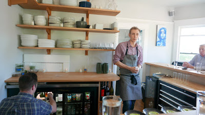At Willow PDX, Chef Doug Weiler retrieving drinks for beverage service while Chef John Pickett welcomes guests