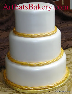 Three tier pearl white fondant custom wedding cake with edible gold rope borders