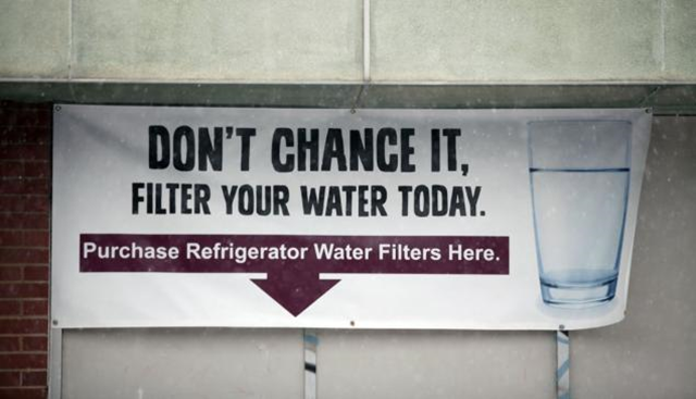 A sign on a the front of a building warns residents to filter their water in Flint, Michigan, where a federal emergency was declared after lead contaminated drinking water. Photo: Bill Pugliano / Getty Images