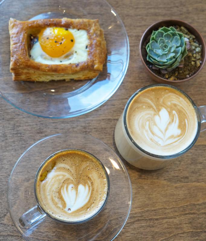 overhead photo of Egg, Prosciutto & Gruyere Tart, Baklava latte, and L'Orange